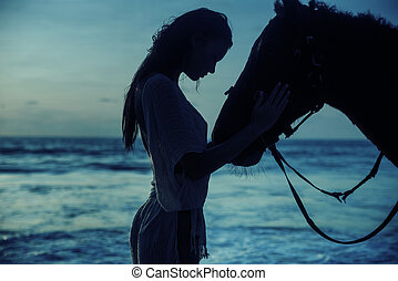 Pretty brunette lady with her horse over the sunset