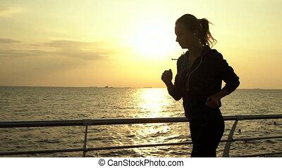Pretty brunette listening to music, running near the sea.