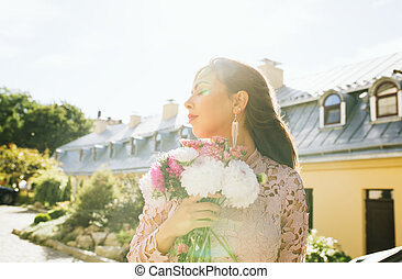 Pretty brunette model in pink dress with flowers in hands on a background of city. Vintage toning effect