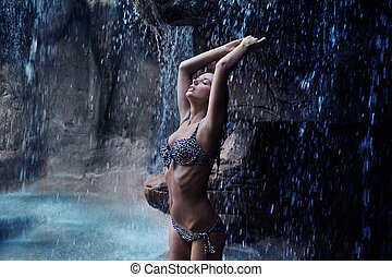Pretty brunette relaxing next to a tropical waterfall