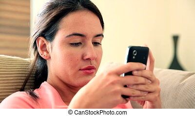 Pretty brunette relaxing on sofa using her smartphone at...