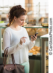 Pretty brunette sending a text at the bakery