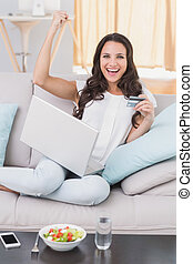 Pretty brunette shopping online on couch