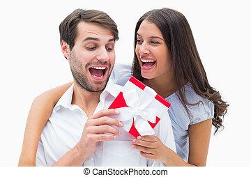 Pretty brunette surprising boyfriend with a gift on white...