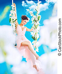 Pretty brunette swinging among white clouds