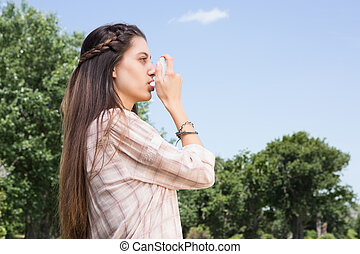 Pretty brunette using her inhaler