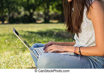 Pretty brunette using laptop in park