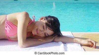 Pretty brunette wearing pink bikini rests on towel