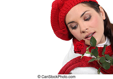 pretty brunette with red rose and assorted winter clothing