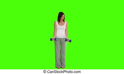 Pretty brunette woman doing bodybuilding against a green...