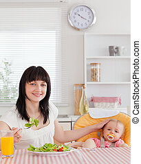Pretty brunette woman eating a salad next to her baby while sitting in the kitchen