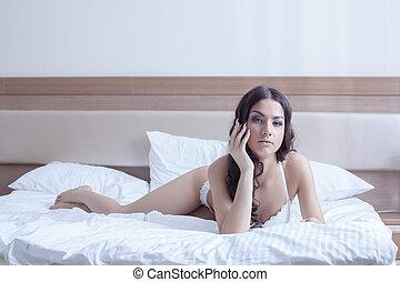 Pretty brunette woman in bedroom