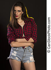 Pretty brunette woman in jeans shorts and plaid shirt