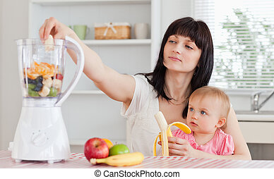 Pretty brunette woman pealing a banana while holding her baby on her knees in the kitchen