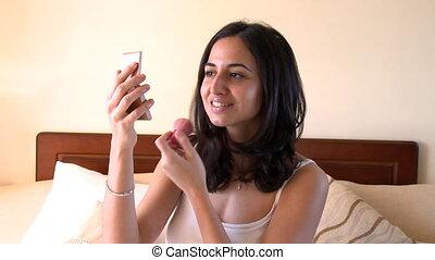 Pretty brunette woman putting blush