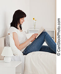 Pretty brunette woman reading a book while sitting on a bed