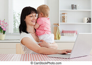 Pretty brunette woman relaxing with her laptop next to her baby while sitting in the kitchen