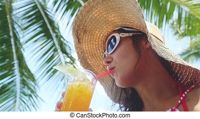 Pretty brunette woman wearing sunglasses and hat with tropical cocktail on the beach enjoying sunny weather in slow motion, 1920x1080