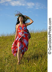 Pretty brunette woman with long hair in red dress and wreath of flowers coming down the hill against blue sky