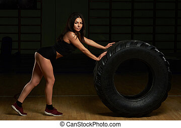 Pretty brunette work out with tire