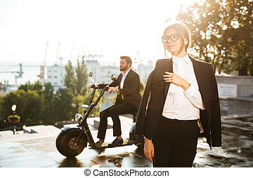 Pretty business woman posing outdoors with man in suit