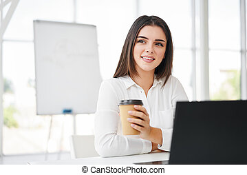 Pretty business woman with cup of coffee relax during break time