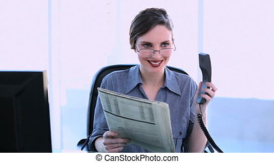 Pretty businesswoman answering phone and reading newspaper...