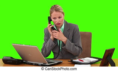 Pretty businesswoman at her desk making an appointment with somebody