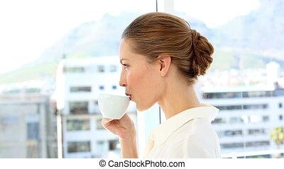 Pretty businesswoman drinking