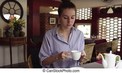 Pretty businesswoman drinking tea and relaxing in cafe