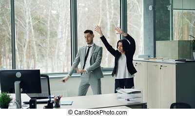 Pretty businesswoman is teaching her male coworker to dance listening to music and moving in office enjoying break from work. People are wearing suits.