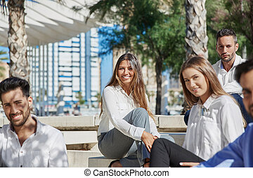 Pretty businesswoman sitting with coworkers outside smiling