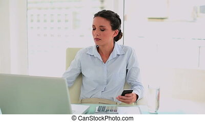 Pretty businesswoman texting