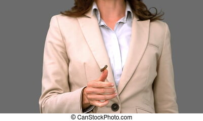 Pretty businesswoman throwing a coin on grey screen in slow...