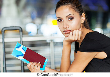 pretty businesswoman with air ticket at airport waiting for...