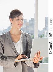 Pretty businesswoman working on laptop