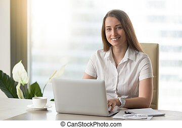 Pretty businesswoman working on laptop, smiling for camera at wo