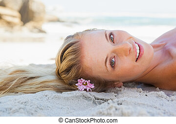 Pretty carefree blonde lying on the beach on a sunny day