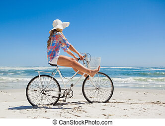 Pretty carefree blonde on a bike ride at the beach on a ...