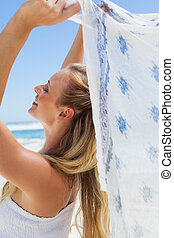 Pretty carefree blonde posing on the beach with scarf