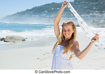 Pretty carefree blonde smiling at camera on the beach with scarf