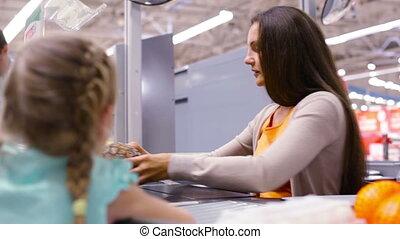 Pretty cashier provide service to the customer, little girl...