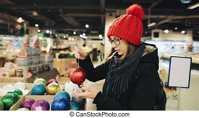 Pretty caucasian girl in glasses and a red hat chooses the balls for the Christmas in the market and playing with one of them smiling looking to the camera. A woman is bying colorful decorations.