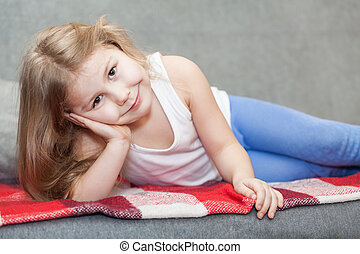 Pretty Caucasian little girl lying on the sofa