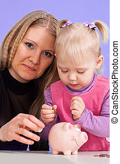 Pretty Caucasian mother with her daughter play with the piggy bank on a light background