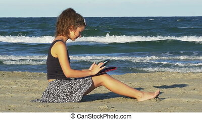 Pretty Caucasian woman having fun with her tablet pc by the sea