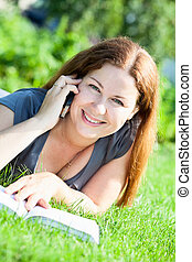 Pretty Caucasian young woman portrait speaking on phone with book on green grass