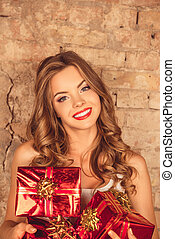 Pretty cheerful girl with red lips holding presents and smiling