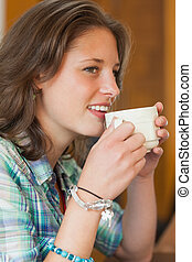 Pretty cheerful student drinking a cup of coffee