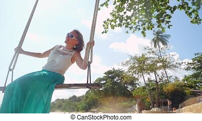Pretty cheerful woman wearing sunglasses relaxes on the swing at the stones beach in slow motion.